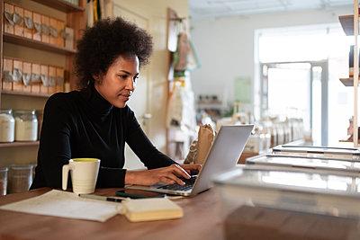 Smart black entrepreneur using laptop in shop - p1166m2224281 by Cavan Images