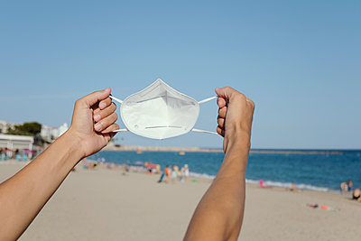 Man with a FFP2 face mask in his hands on the beach - p1423m2210324 by JUAN MOYANO
