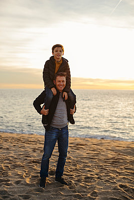 Portrait of father carrying son piggyback on the beach - p300m1562928 by Bonninstudio