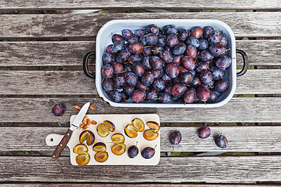 Fresh plums in casserole and chopped plums on chopping board - p300m1568058 von Gaby Wojciech