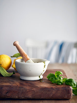 Pestle and mortar with pesto and basil on cutting board - p429m1418485 by Debby Lewis-Harrison