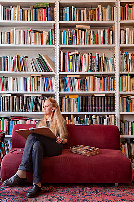 Caucasian woman sitting on sofa sketching - p555m1480112 by Peter Dressel