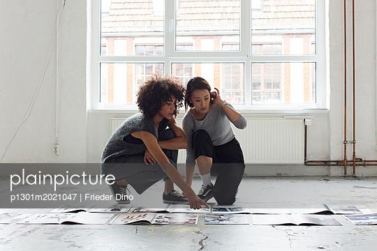 Mädels hocken über dem Boden und schauen sich Mgazine an - p1301m2021047 von Delia Baum