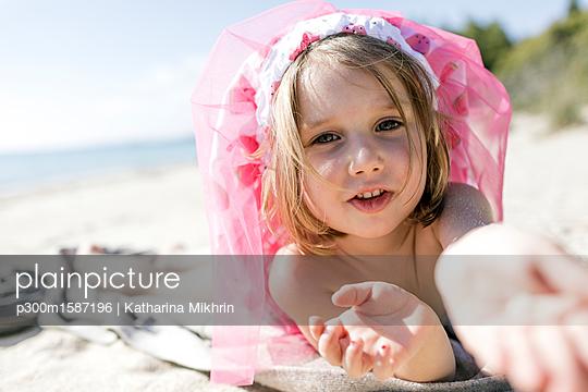 Portrait of little girl lying on the beach - p300m1587196 von Katharina Mikhrin
