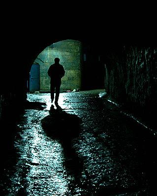mann in dunkler gasse mit torbogen - p627m1035892 von Murat Yazar