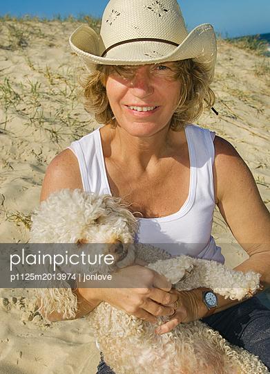 Woman and dog on beach - p1125m2013974 by jonlove