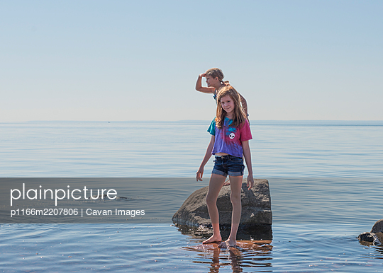 Two Young Girls on Rocky Shoreline - p1166m2207806 by Cavan Images