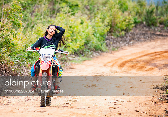 woman riding her dirt-bike on forest track in Pak Chong / Thailand - p1166m2207924 by Cavan Images