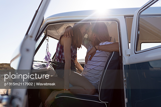 Young couple kissing each other in front seat of camper van at beach - p1315m2117902 by Wavebreak