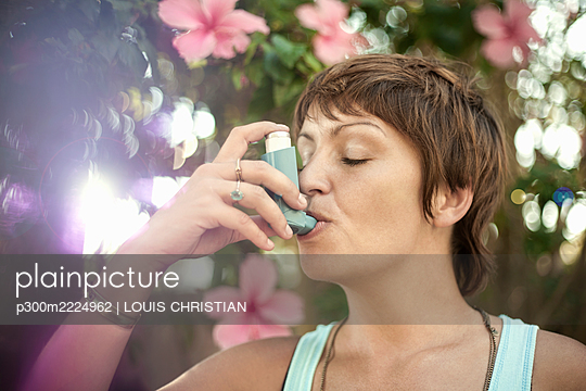 Young woman breathing through asthma inhaler - p300m2224962 by LOUIS CHRISTIAN