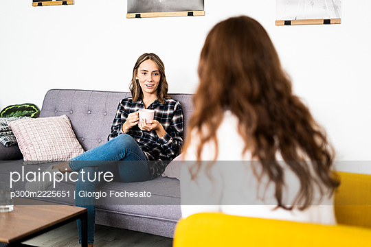 Young woman holding coffee cup while talking with friend at home - p300m2225651 by Giorgio Fochesato