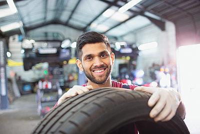 Portrait confident male mechanic with tire in auto repair shop - p1023m2196735 by Tom Merton
