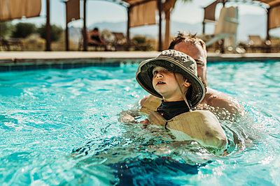Close up of young toddler boy and father swimming in pool on vacation - p1166m2218223 by Cavan Images