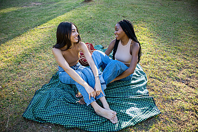 Two teenage girls sitting on picnic blanket in the park - p1640m2259883 by Holly & John