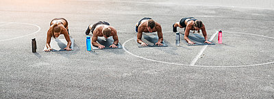 Sporty team during workout, plank - p300m2069941 by Epiximages