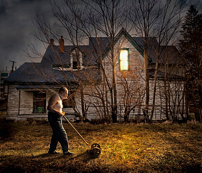 Caucasian man mowing lawn outside home - p555m1454207 by Chris Clor