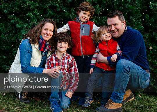 A happy family snuggle together for a family portrait outside - p1166m2112873 by Cavan Images