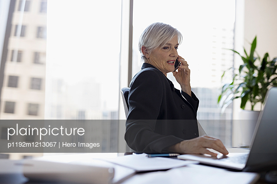 Senior female lawyer working at laptop and talking on cell phone