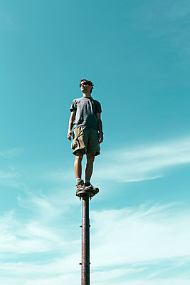 Man standing and balancing on metal post, looking towards expansive sky, Surprise Mountain, Alpine Lakes Wilderness, Mt. Baker-Snoqualmie national forest. - p1100m875963f by Paul Edmondson
