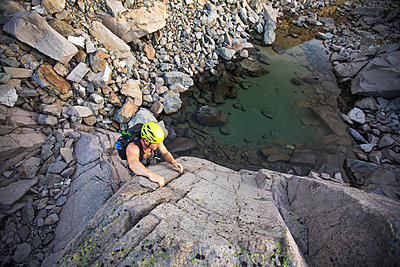 high angle of man bouldering above small alpine tarn. - p1166m2095228 by Cavan Images