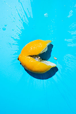 a lemon smashed against a blue background resembling a smiley face - p1423m2076789 by JUAN MOYANO