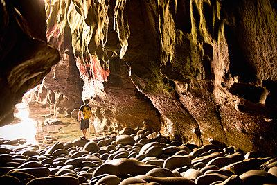 Teenage boy exploring care with rocks in La Jolla, California - p1427m2109936 by Stephen Simpson