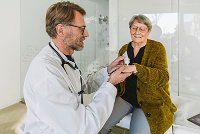 Doctor putting ointment on hand of senior patient - p300m2180534 by Mareen Fischinger