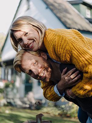 Portait of happy man giving his wife a piggyback ride in garden - p300m2205522 by Kniel Synnatzschke