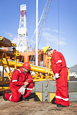 Workers on oil rig examining equipment - p42915020f by Hybrid Images