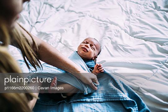 overhead shot of newborn baby being wrapped in blanket - p1166m2200260 by Cavan Images