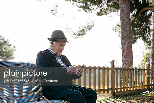 Old man with, sitting on bench, using smartphone