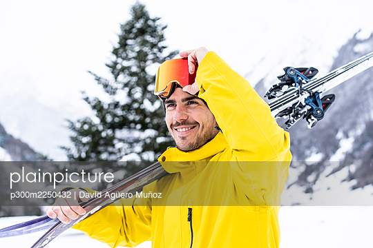 Smiling man with ski looking away while standing on snow covered valley - p300m2250432 by David Agüero Muñoz