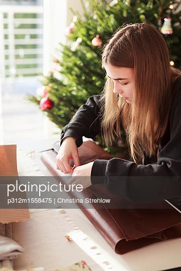 plainpicture - plainpicture p312m1558475 - Girl packing Christmas gift - plainpicture/Johner/Christina Strehlow
