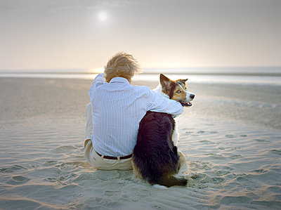 Man on beach with dog - p1207m1109472 by Michael Heissner