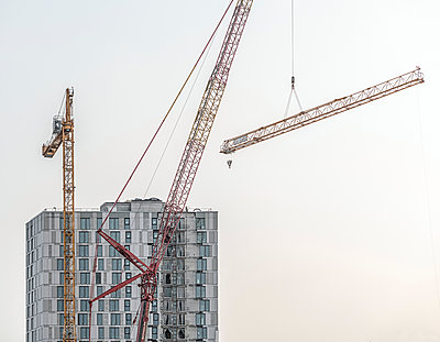 Crane transports a load, construction site - p1292m2272660 by Niels Schubert