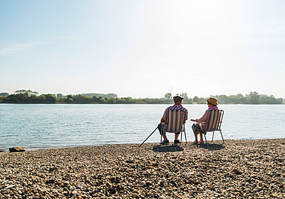 Germany, Ludwigshafen, back view of senior couple sitting side by side on folding chairs at riverside - p300m1068784f by Uwe Umstätter