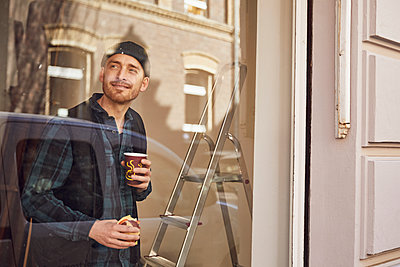 Man refurbishing shop location, drinking coffee, looking out of window - p300m2189341 by Maya Claussen