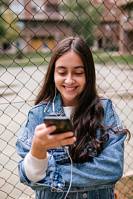 Smiling teenage girl using mobile phone while standing against chainlink fence at sports court - p300m2198360 by LUPE RODRIGUEZ