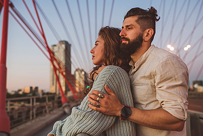 Contemplated couple looking away while standing on bridge in city during sunset - p300m2220820 by Ekaterina Yakunina