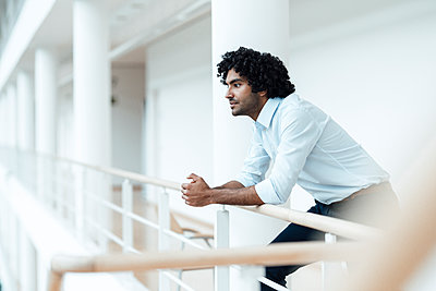 Thoughtful young male entrepreneur with black curly hair leaning on railing at office corridor - p300m2243718 by Joseffson