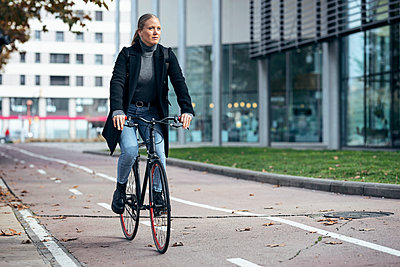 Woman doing cycling on road by modern building - p300m2256038 by Josep Suria