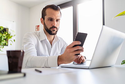 Young entrepreneur with laptop using mobile phone while sitting at office - p300m2264882 by Daniel Ingold