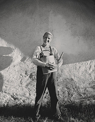 Portrait of mature woman holding watering can - p312m764826 by Bruno Ehrs