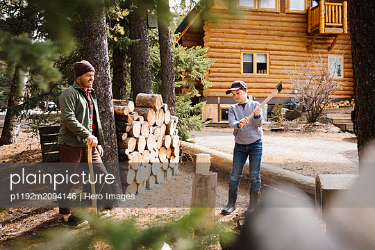 Father teaching son how to cut firewood outside cabin - p1192m2094146 by Hero Images