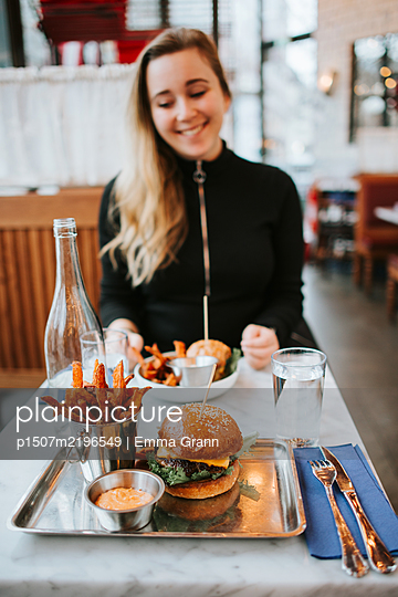 Young woman sits in fast food restaurant - p1507m2196549 by Emma Grann