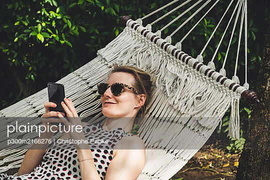 Smiling woman lying in a hammock using cell phone - p300m2166276 by Christophe Papke