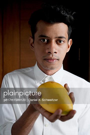 Mann hält eine frische Mango - p817m1589120 von Daniel K Schweitzer