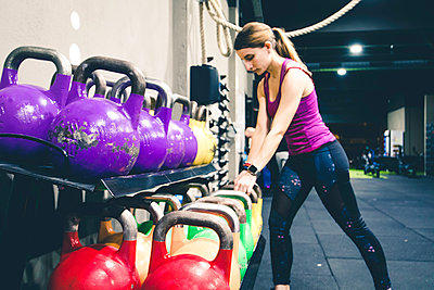 Young girl grabbing kettlebell at a crossfit gym - p1166m2146389 by Cavan Images