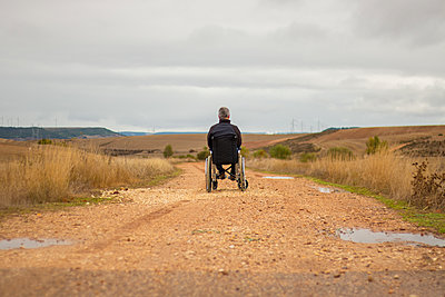 Rear vision of a disabled man in a wheelchair alone in a path - p1166m2146689 by Cavan Images