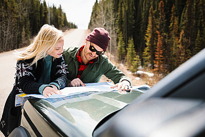 Couple looking at map on hood of car at sunny roadside - p1192m2094119 by Hero Images